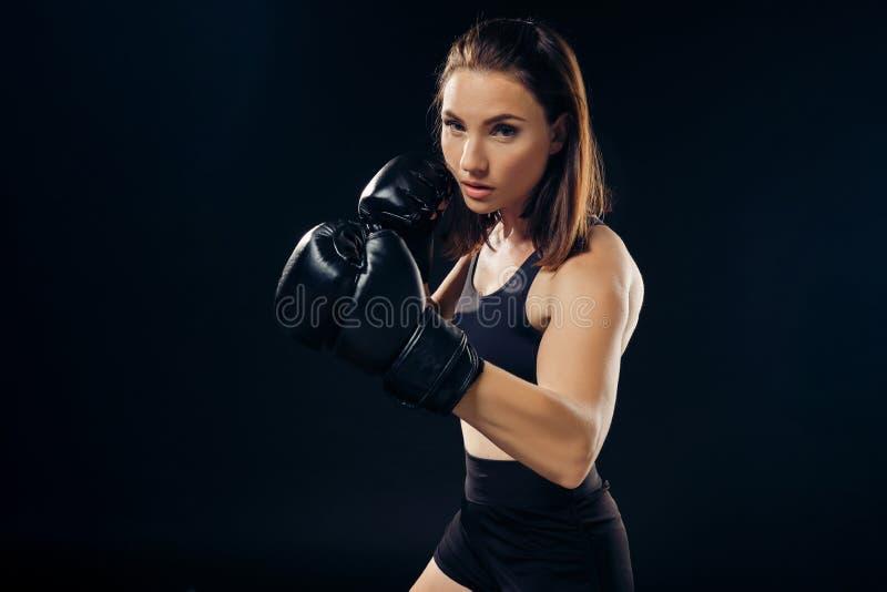 La femme sportive dans des gants de boxe pratique le karaté dans le studio photos libres de droits