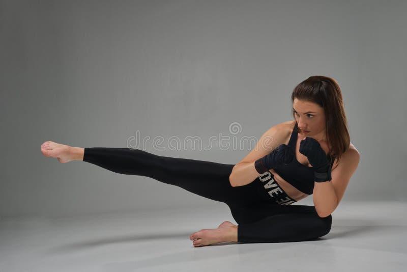 La femme sportive dans des mitaines de boxe pratique le karaté dans le studio photo stock