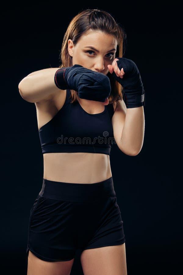 La femme sportive dans des mitaines de boxe pratique le karaté dans le studio photographie stock