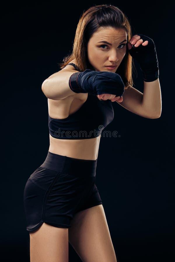 La femme sportive dans des mitaines de boxe pratique le karaté dans le studio photo libre de droits