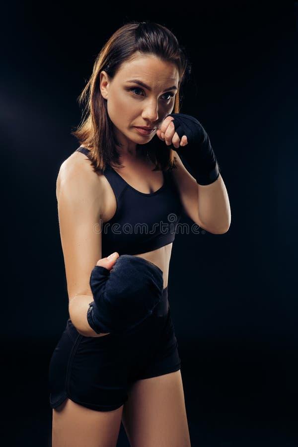 La femme sportive dans des mitaines de boxe pratique le karaté dans le studio image libre de droits