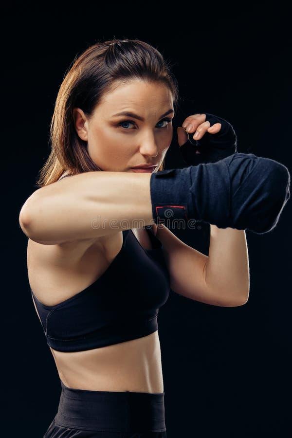 La femme sportive dans des mitaines de boxe pratique le karaté dans le studio photos stock