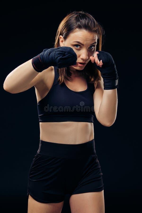 La femme sportive dans des mitaines de boxe pratique le karaté dans le studio photographie stock libre de droits