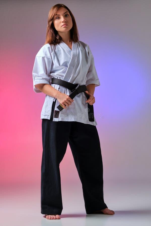 La femme sportive dans le kimono traditionnel pratique le karaté dans le studio photographie stock