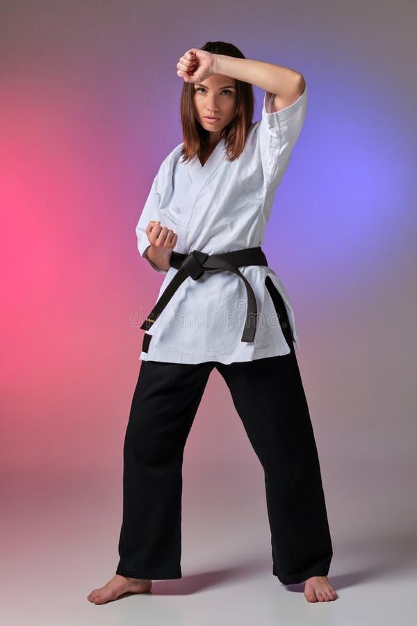 La femme sportive dans le kimono traditionnel pratique le karaté dans le studio photos stock