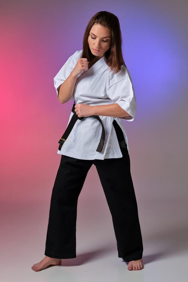 La femme sportive dans le kimono traditionnel pratique le karaté dans le studio photos libres de droits