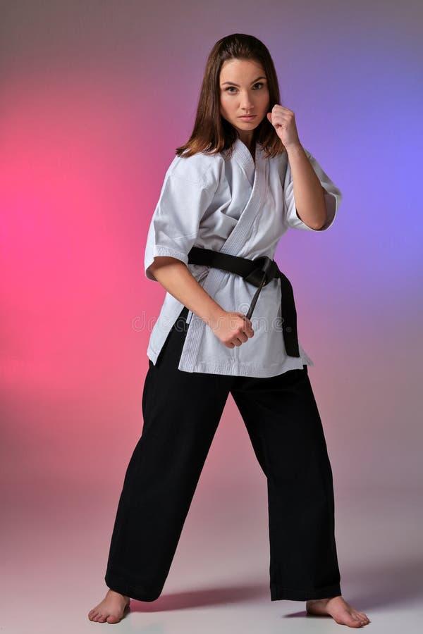La femme sportive dans le kimono traditionnel pratique le karaté dans le studio images libres de droits