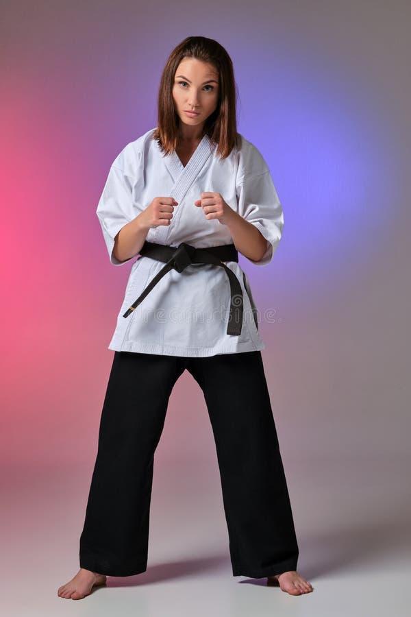 La femme sportive dans le kimono traditionnel pratique le karaté dans le studio photo libre de droits
