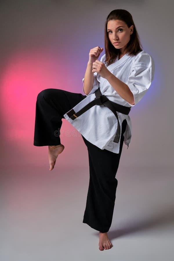 La femme sportive dans le kimono traditionnel pratique le karaté dans le studio photographie stock libre de droits