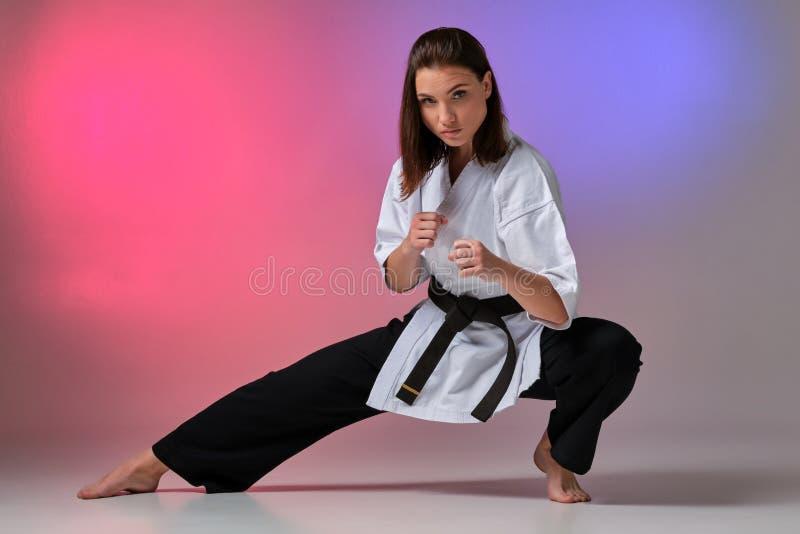 La femme sportive dans le kimono traditionnel pratique le karaté dans le studio image stock