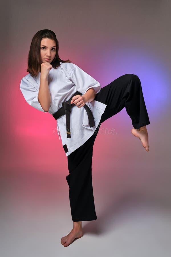 La femme sportive dans le kimono traditionnel pratique le karaté dans le studio photo stock