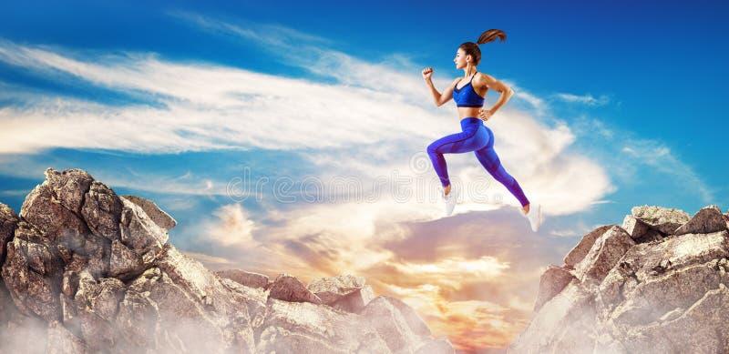 La femme sportive sautent par l'espace entre les collines au-dessus du fond de ciel photo libre de droits