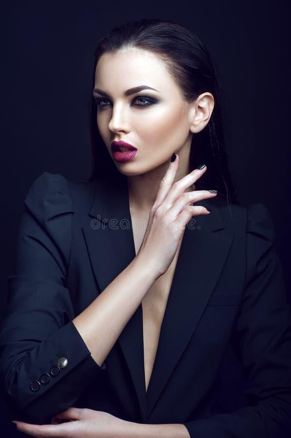 La femme stricte sexy avec le maquillage et la coiffure à la mode pose dans le studio sur le fond noir photos stock