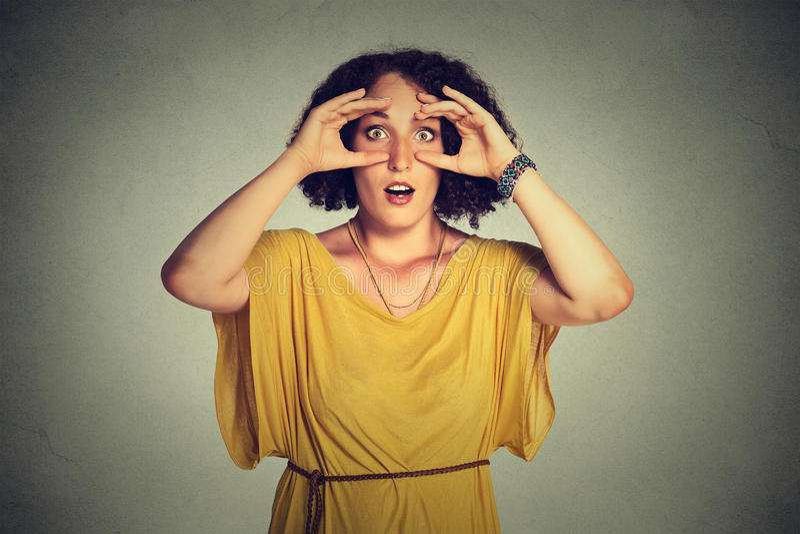 La femme stunned, jetant un coup d'oeil le regard par des doigts aiment la recherche de jumelles images stock