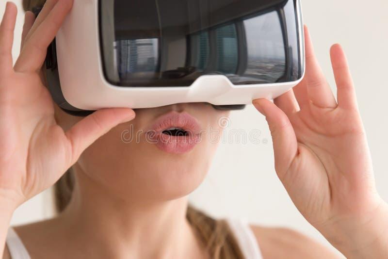 La femme stupéfaite par jeunes portant la pente de casque de VR croient ses yeux photos libres de droits