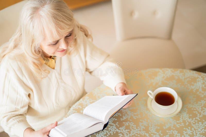 La femme supérieure élégante lit le livre à la table et au thé de avoir images libres de droits