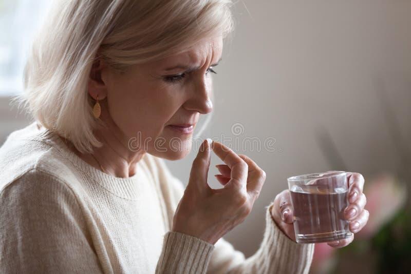 La femme supérieure bouleversée tenant la pilule et le verre arrosent prendre la médecine photos stock