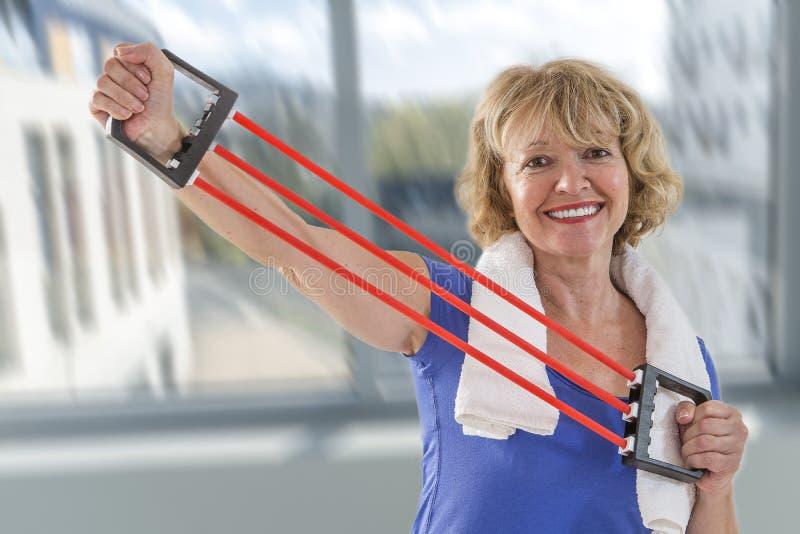 La femme supérieure convenable employant la résistance élastique se réunit avec des bras image stock