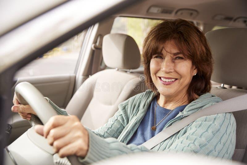 La femme supérieure dans le siège de conduite regardant l'appareil-photo, se ferment  images stock