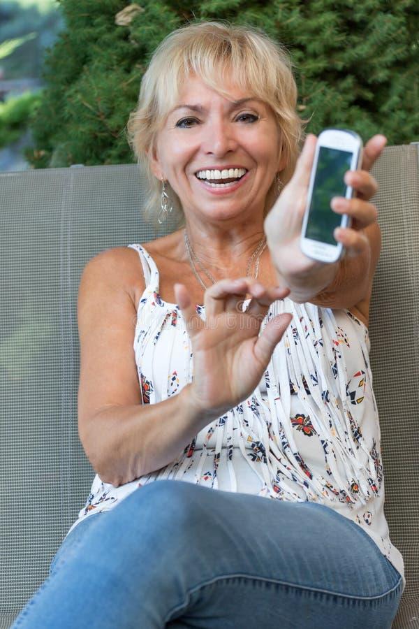 La femme supérieure de sourire montre son téléphone intelligent photos stock