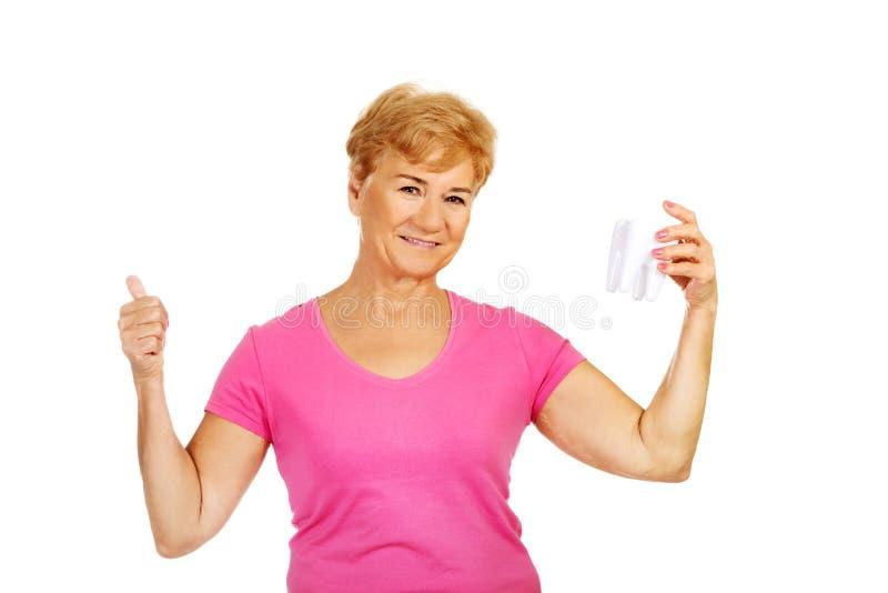 La femme supérieure de sourire tenant une dent modèlent et des expositions CORRECT images libres de droits