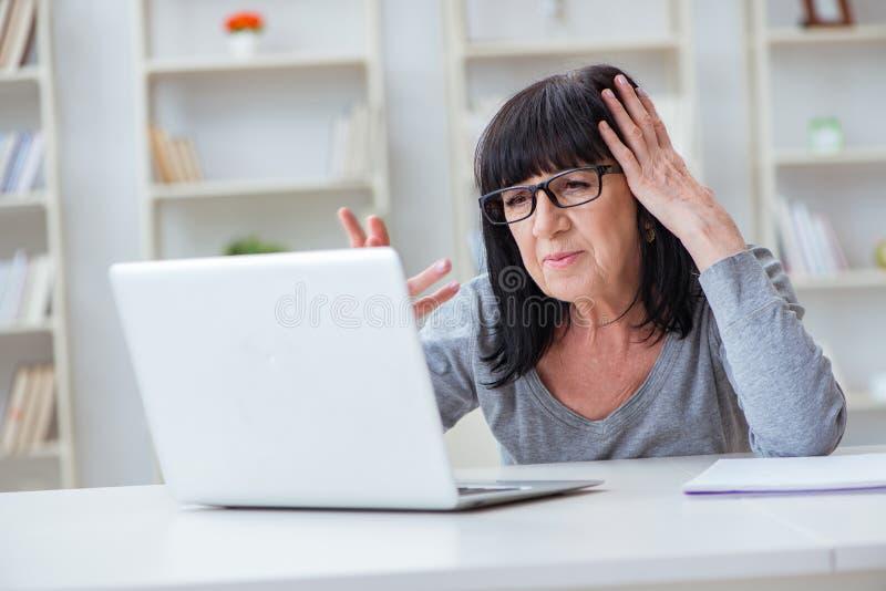 La femme supérieure luttant à l'ordinateur photo stock