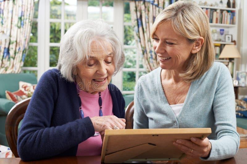 La femme supérieure regarde la photo dans le cadre avec le voisin féminin mûr images libres de droits