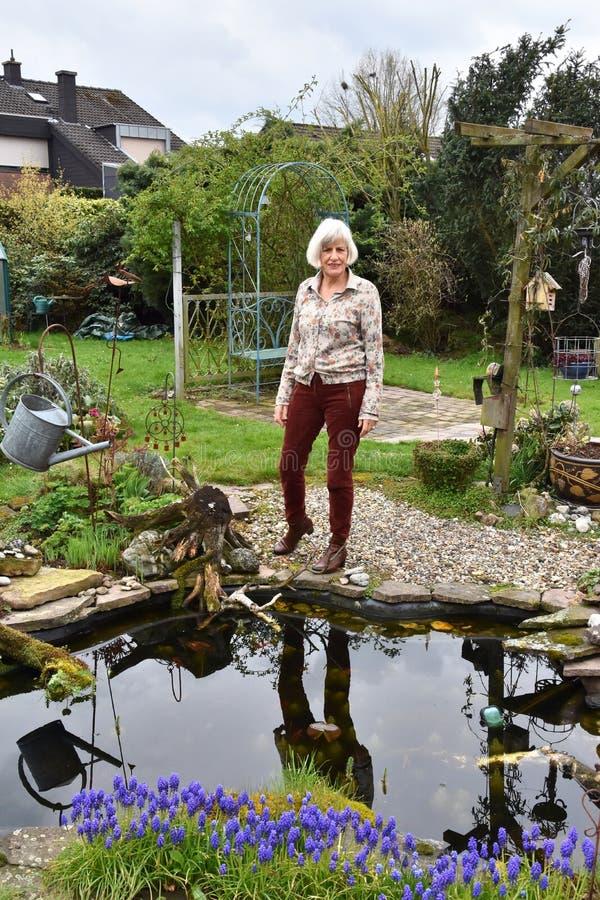 La femme supérieure se tient à son étang de jardin image stock