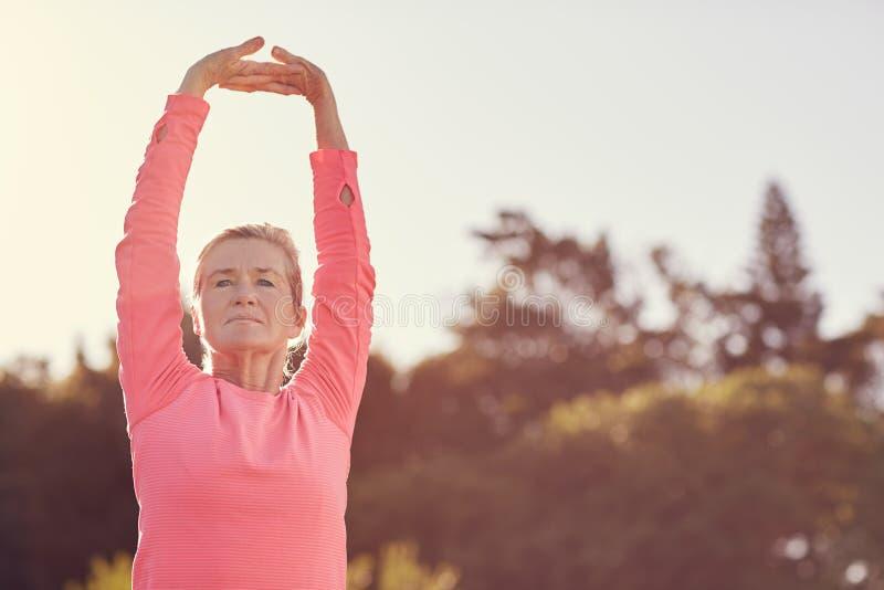La femme supérieure sportive faisant l'échauffement d'exercice s'étire dehors photo stock