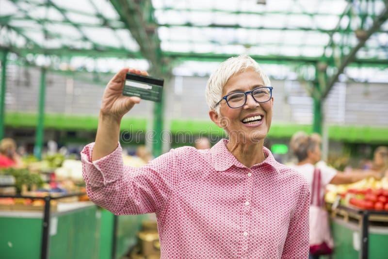 La femme supérieure tient la carte de crédit photographie stock