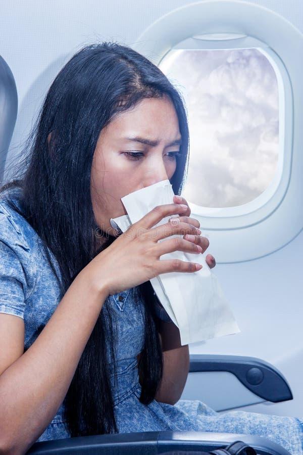 La femme sur l'avion a vomi dans un sac de papier photos libres de droits
