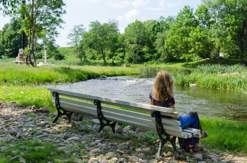 La femme sur le banc admirent le courant rapide d'eau de rivière d'écoulement image libre de droits