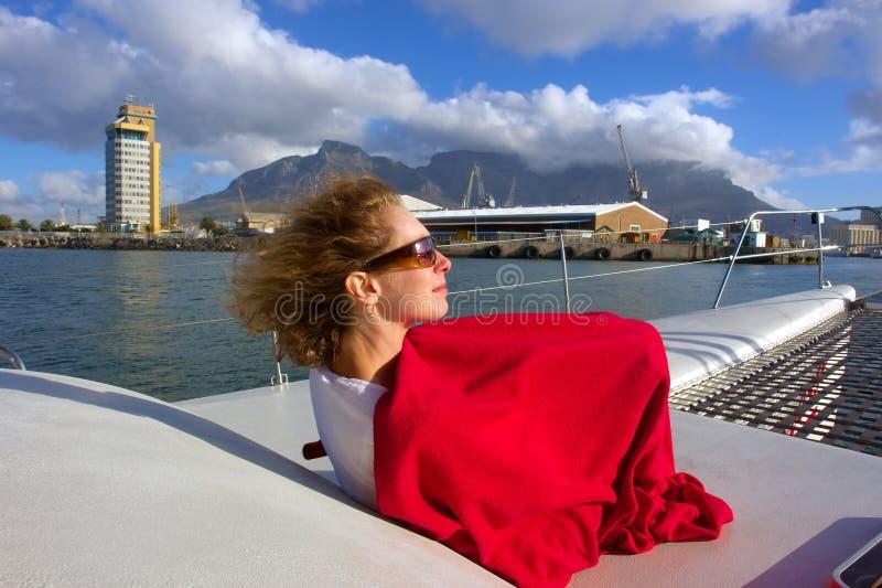 La femme sur le bureau du yacht apprécie la lumière de coucher du soleil photo libre de droits