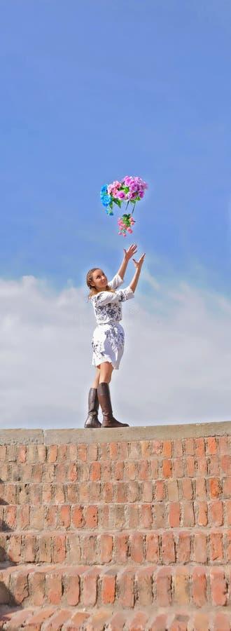 La femme sur les étapes attrape les fleurs colorées image stock