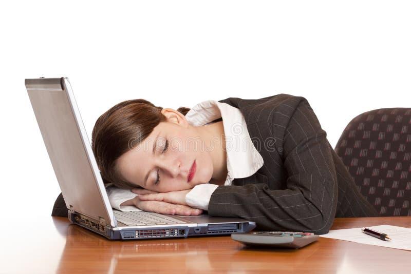La femme surchargée fatiguée d'affaires dort sur l'ordinateur portatif images libres de droits