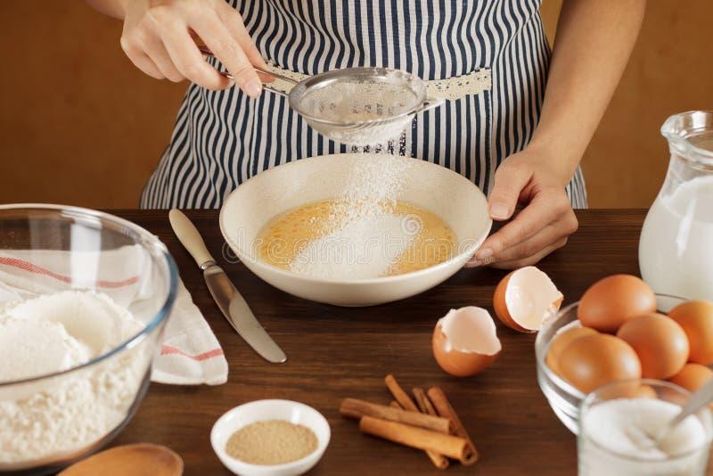 La femme tamise la farine dans la cuvette avec les oeufs et le lait mélangés photo stock