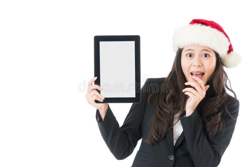 La femme tenant le comprimé numérique a excité le chapeau de port de Santa photos stock