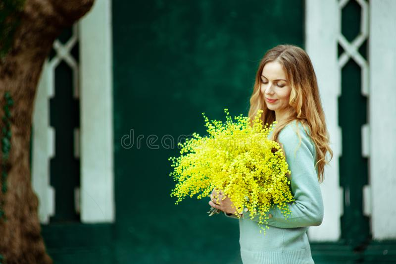 La femme tenant un bouquet de mimosa, le 8 mars cadeau, célèbrent l'amour vivant photographie stock libre de droits