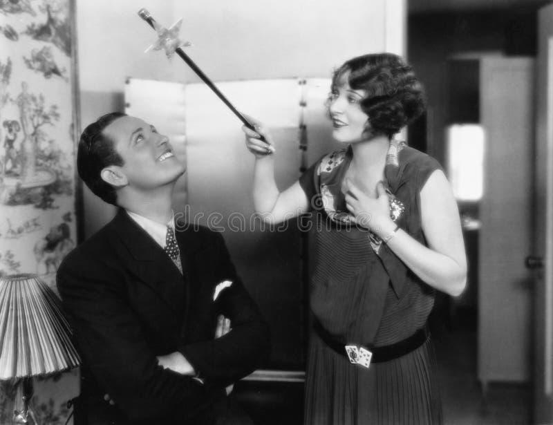 La femme tenant une baguette magique magique au-dessus de ses amis se dirigent (toutes les personnes représentées ne sont pas plu photographie stock libre de droits