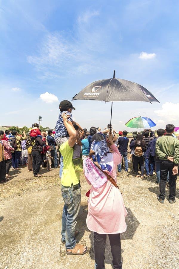La femme a tenu le parapluie pour son mari et fils tout en observant l'exposition acrobatique aérienne au salon de l'aéronautique photographie stock libre de droits