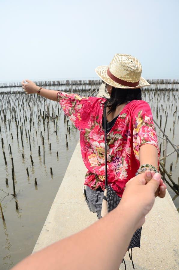 La femme thaïlandaise mènent quelqu'un par la main et se tiennent sur le pont en passage couvert images libres de droits