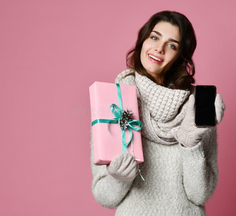 La femme tient des boîtes et montre le téléphone portable d'écran vide au-dessus du fond rose photo libre de droits