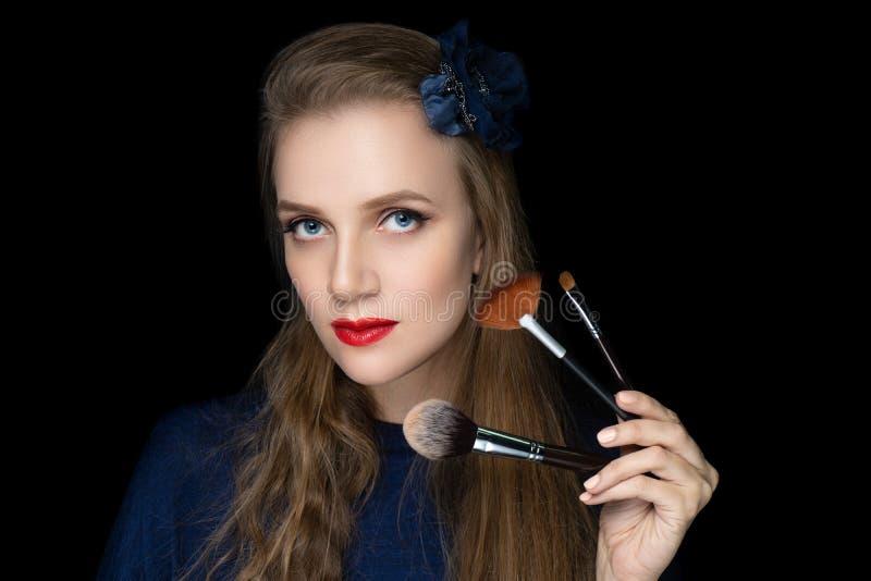 La femme tient des brosses de maquillage dans des ses mains photo stock