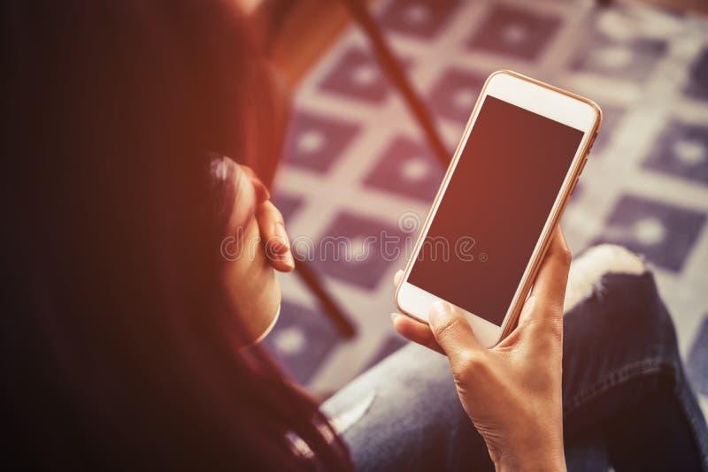 La femme tient le café potable mobile vide d'écran tactile image libre de droits