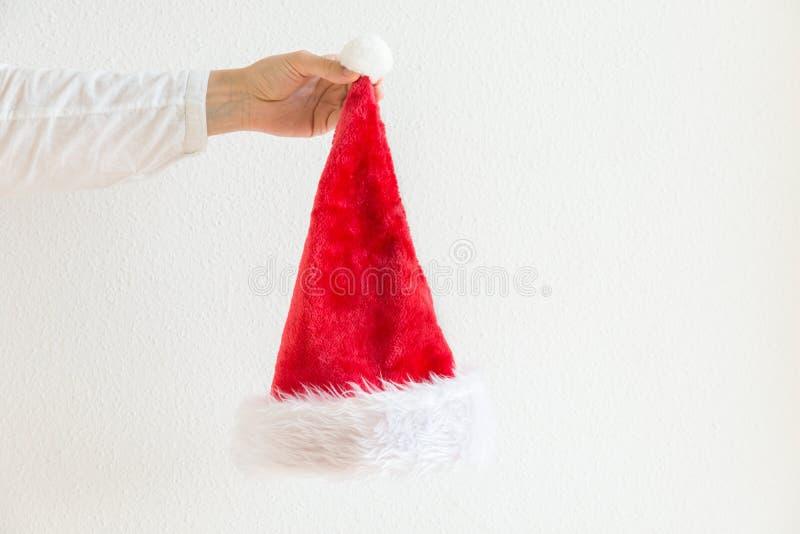 La femme tient le fond blanc pelucheux disponible de mur de Santa Claus Hat Bannière d'affiche de nouvelles années de Noël images stock