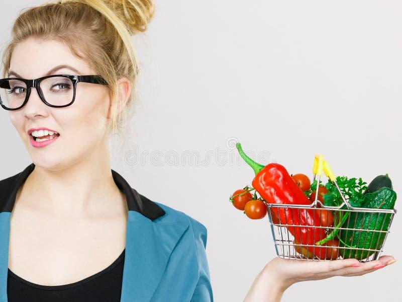 La femme tient le panier à provisions avec des légumes images stock