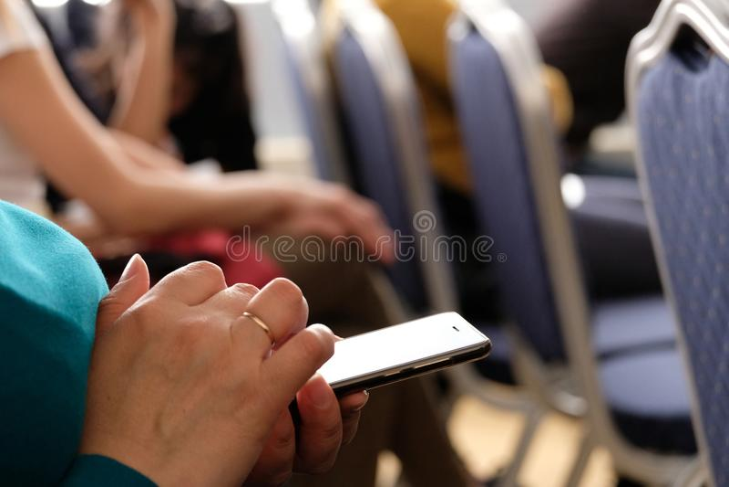 La femme tient le téléphone dans sa main dans la salle de conférences et veut appeler ou observer le message photos libres de droits