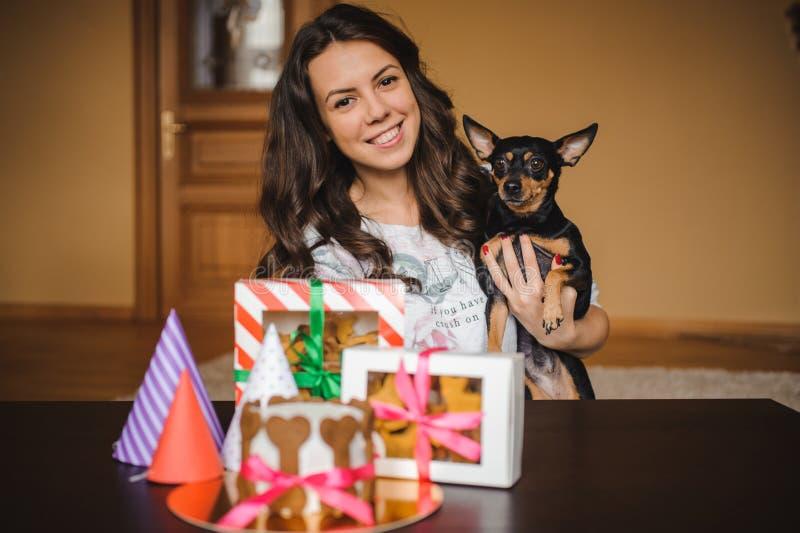 La femme tient le terrier de jouet avec le gâteau et les biscuits de chien sur la fête d'anniversaire image stock