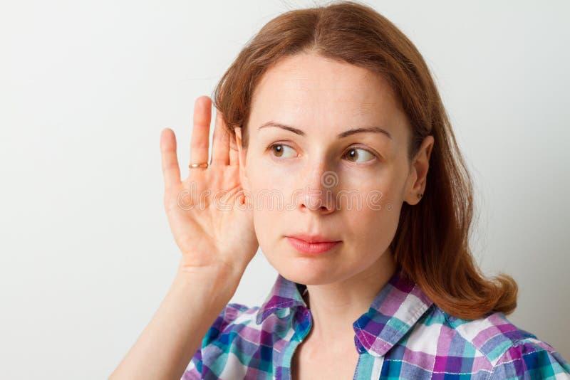 La femme tient sa main près de l'oreille et écoute photographie stock libre de droits