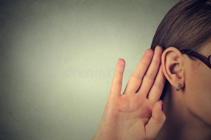 La femme tient sa main près de l'oreille et écoute soigneusement image libre de droits